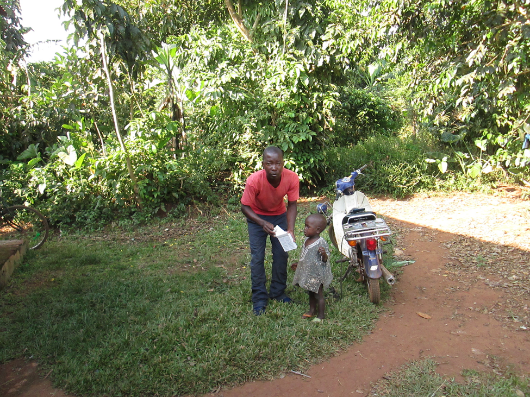 A CHW takes a sick child to the health facility Uganda