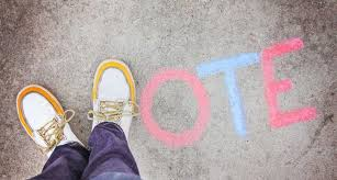 An image of some feet over the word vote chalked on the pavement